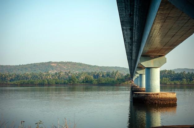 Lange straßenbrücke über den fluss, seitenansicht. kraftvolle steinsäulen der brücke spiegeln sich im flusswasser gegen das mit grünen bäumen bedeckte ufer.