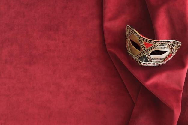 Lange venezianische maske auf einem roten stoff