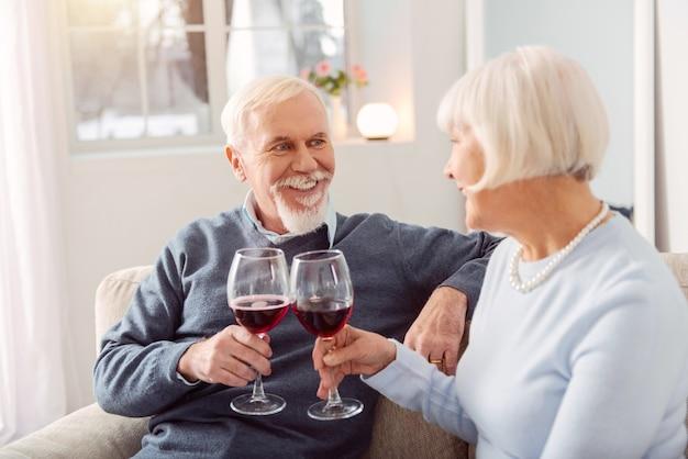 Lange zusammen. glückliches älteres paar, das ihren hochzeitstag feiert und wein trinkt, während sie einander mit liebe betrachten