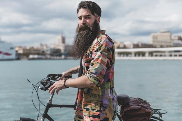 Langer bärtiger junger mann, der mit fahrrad nahe der küste steht
