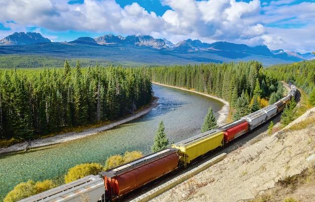 Langer fracht comtainer zug, der entlang bogenfluß in kanadischen rocky mountains, nationalpark banff, kanadische rocky mountains, kanada sich bewegt