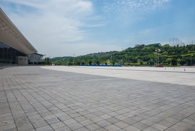 Langer leerer fußweg im modernen stadtplatz mit skyline