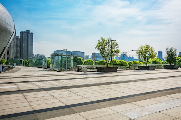 Langer leerer fußweg im modernen stadtplatz mit skyline.