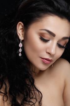 Langer Ohrring mit violetten Edelsteinen hängt am Ohr der Frau
