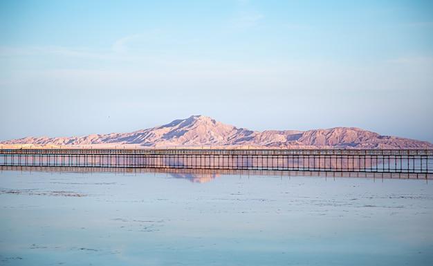 Langer pier zwischen meer und bergen. der himmel spiegelt sich im wasser.