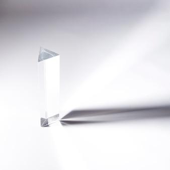 Langer prismakristall mit dunklem schatten auf weißem hintergrund