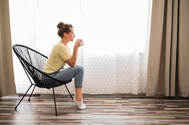 Langer schuss der frau, die auf stuhl sitzt