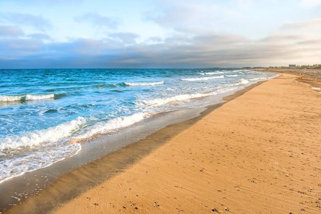 Langer tropischer sandstrand mit brandung und meereswellen