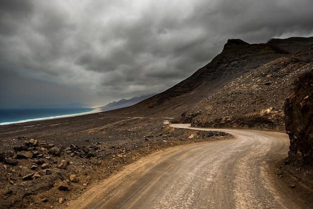 Langer unendlicher off-road-pfad wilder strand und berge bestimmungsort alternativer ort für reiseurlaub verloren im fernweh die welt auf andere weise erkunden schöne landschaft mit ozean