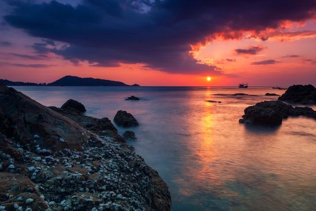Langes belichtungsbild des drastischen himmelmeerblicks mit felsen in der sonnenunterganglandschaft