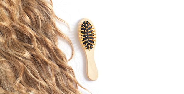 Langes blondes gewelltes haar und bürste isoliert auf weiß