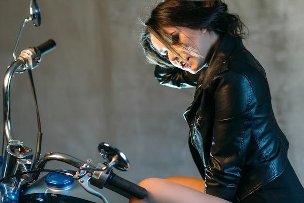Langes dunkles haar des sexy durchdachten damenesprits wirft in der lederjacke auf einem motorrad auf