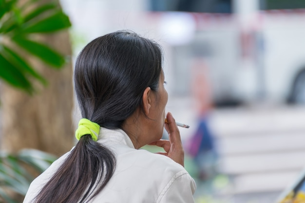 Langes haar der asien-frauen, das im park raucht