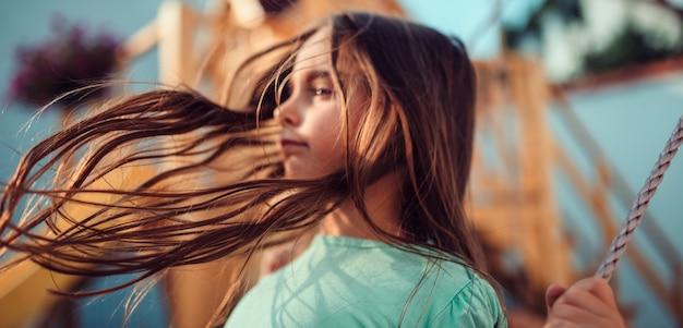 Langes haar des kleinen mädchens, das in die luft fliegt, während sie auf schwingen sitzt