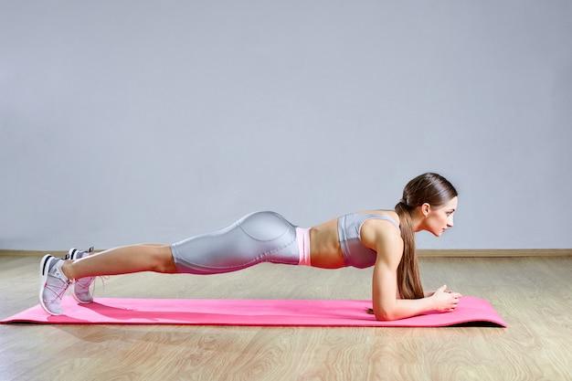 Langes haar weiblich, das statische übung der planke im fitnessstudio liegt, das auf matte liegt