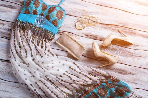 Langes kleid und clutch. beige absatzschuhe und kleid. stilvolle kleidung unter sonnenlicht. verkauf von qualitätswaren.