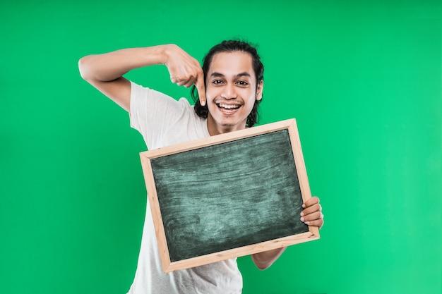 Langes schwarzes haar des jungen mannes, das etwas auf einer leeren tafel an einer grünen wand hält und zeigt