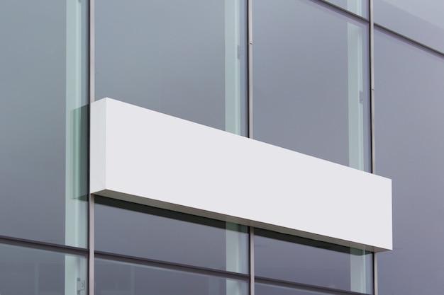 Langes weißes shop-banner-schild, das an der glasoberfläche des bürogebäudes hängt