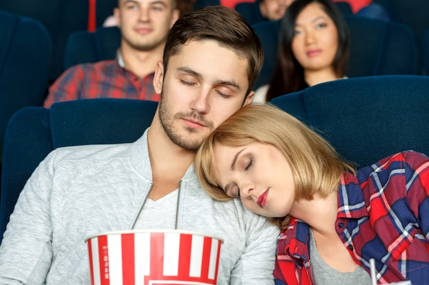 Langeweile beim schlafen. nahaufnahme schoss von einem schönen jungen paar, das während der filme in einem lokalen kino schläft