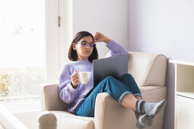 Langeweile, zu hause zu bleiben. junge berufstätige frau oder studentin im sessel im schlafzimmer, die ein online-treffen hat und eine tasse kaffee hält.