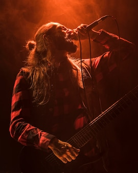 Langhaar-gitarrist, der niedrige ansicht singt