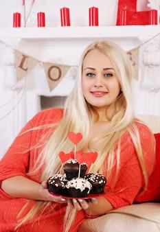 Langhaarige blondine mit festlichem dessert zum valentinstag