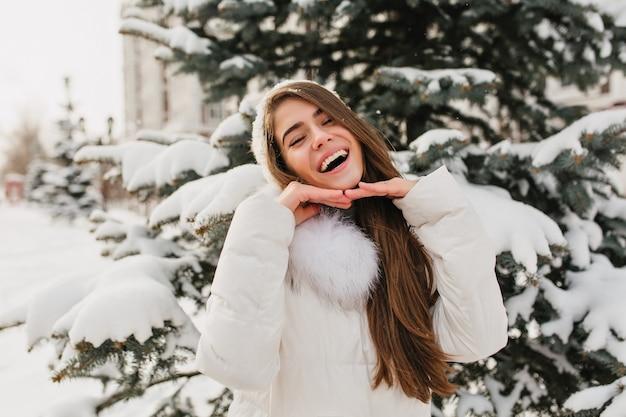 Langhaarige brünette frau, die mit glücklichem gesichtsausdruck im wintermorgen aufwirft. außenporträt des reizenden europäischen weiblichen modells im weißen hut, der spaß auf schneebedeckter fichte hat