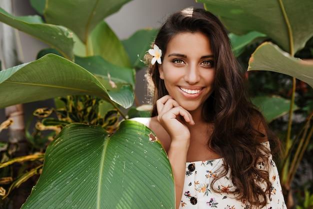 Langhaarige brünette frau in guter stimmung posiert mit einem lächeln zwischen tropischen pflanzen