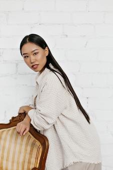 Langhaarige brünette gebräunte asiatin in stylischer strickjacke und hose lehnt sich auf sessel und posiert auf weißer backsteinmauer
