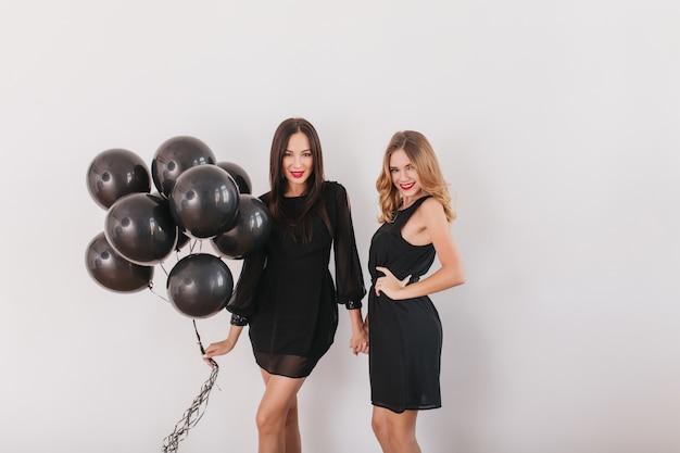 Langhaarige damen mit schlauem lächeln posieren mit partyballons isoliert in weißer wand