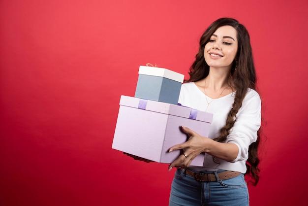 Langhaarige frau, die mit geschenkboxen auf rotem hintergrund steht. foto in hoher qualität