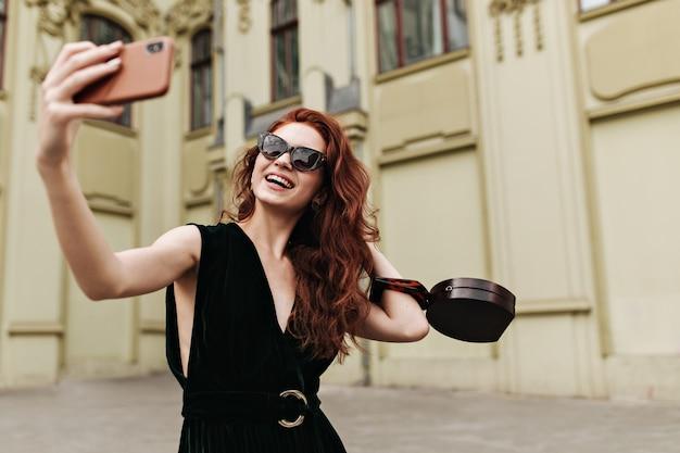 Langhaarige frau mit sonnenbrille nimmt selfie nach draußen