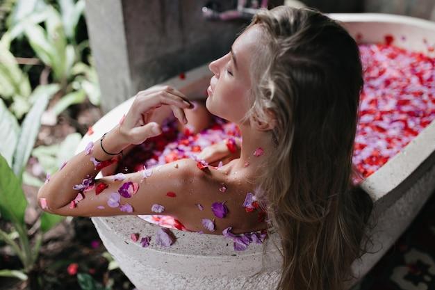 Langhaarige gebräunte frau, die am wochenende spa genießt. blondes weibliches modell, das im bad mit blütenblättern liegt und mit geschlossenen augen kühlt.