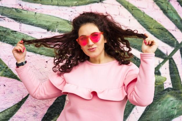 Langhaarige gelockte brunettefrau im rosa kleid und in den rosa gläsern schaut spaß mit einem schielen.
