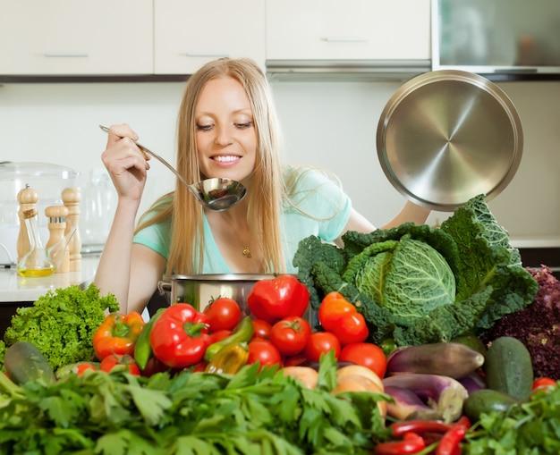 Langhaarige hausfrau kocht mit frischem gemüse