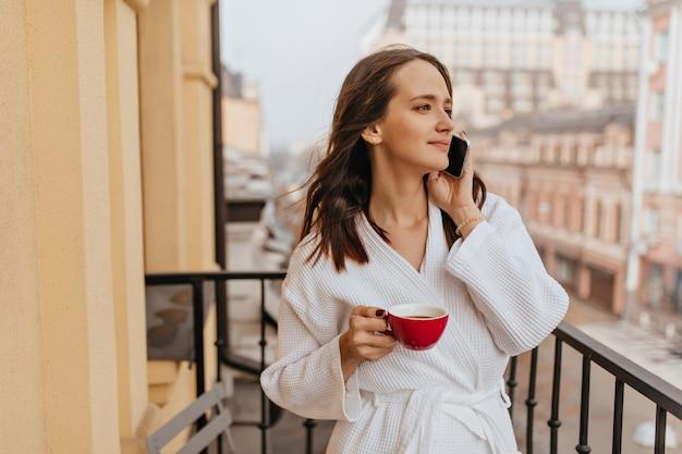 Langhaarige junge frau, die blick auf stadt auf balkon genießt. mädchen im bademantel trinkt kaffee und spricht am telefon.