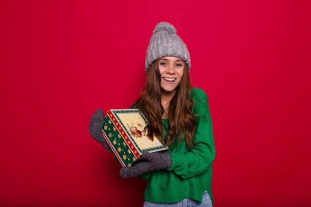 Langhaarige junge frau im grünen pullover und in der grauen strickmütze, die weihnachtsgeschenk auf rot hält