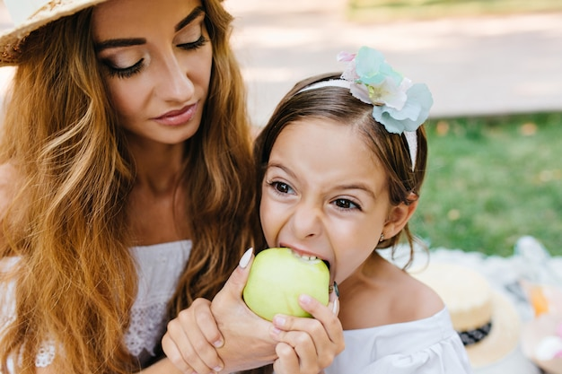 Langhaarige lockige junge frau mit trendiger make-up-fütterungstochter mit grünem apfel. brunette kleines mädchen, das saftige frucht mit großem appetit während des picknicks im park isst.