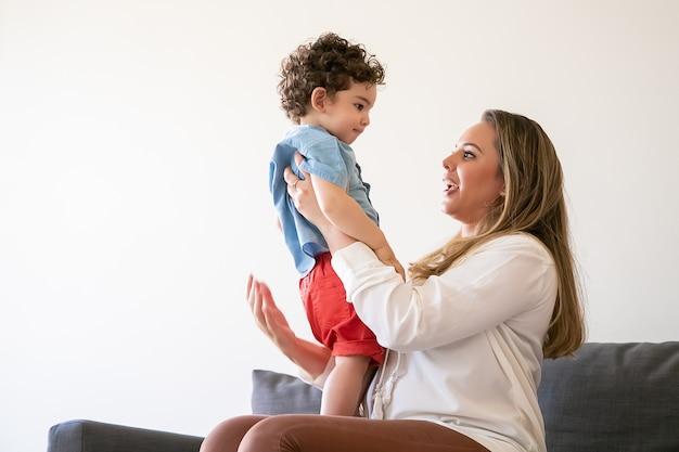 Langhaarige mutter hält kleinen jungen, spricht mit sohn und sitzt auf dem sofa. ernstes kleinkind, das auf mamas knien steht und ihr aufmerksam zuhört. familienzeit, mutterschaft und wochenendkonzept