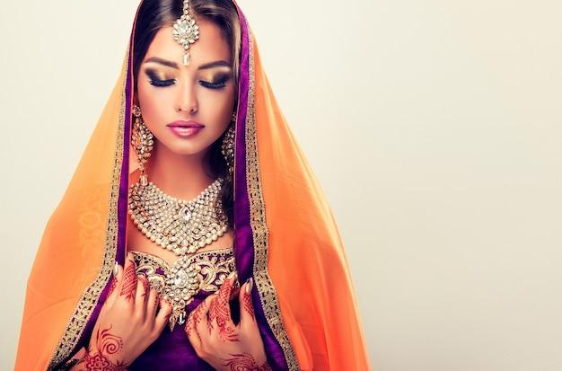 Langhaarige orientalische frau mit mehndi-henna-tattoos an den händen