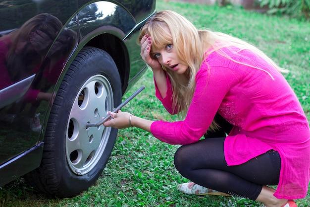 Langhaarige reife blondine, die den reifen auf ihrem auto ändert