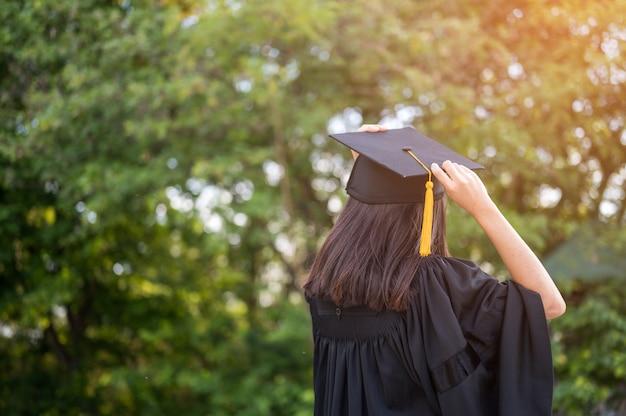 Langhaarige studentinnen, welche die schwarzen rüschenkleider ausdrücken freude auf staffelung an der universität tragen.