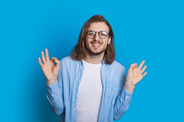 Langhaariger kaukasischer mann mit bart und brille deutet auf das ok-zeichen an einer blauen wand