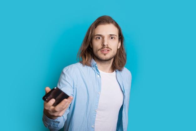 Langhaariger kaukasischer mann mit borsten schaut ernst, während er ein handy an einer blauen wand hält