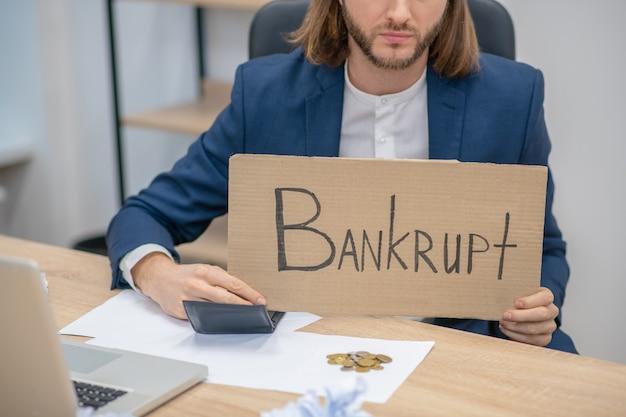 Langhaariger mann mit plakat in den händen über insolvenz im büro, unterer teil des gesichts ist sichtbar