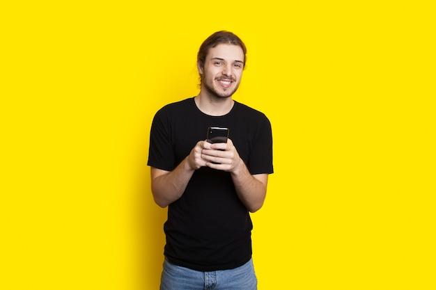 Langhaariger mann plaudert auf einem handy, das kamera an einer gelben studiowand lächelt