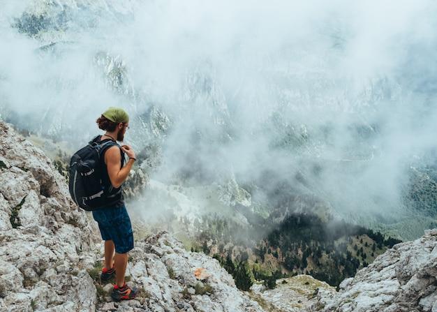 Langhaariger rothaariger junge, der die berge in einer nebeligen landschaft betrachtet