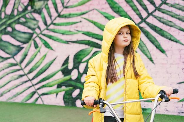 Langhaariges blondes mädchen in einer gelben strickjacke und in einer gelben jacke