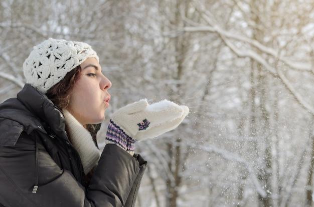 Langhaariges brunettemädchen, das in einen winterpark geht und mit schnee, tragender weißer strickjacke und einem handgemachten weißen hut spielt