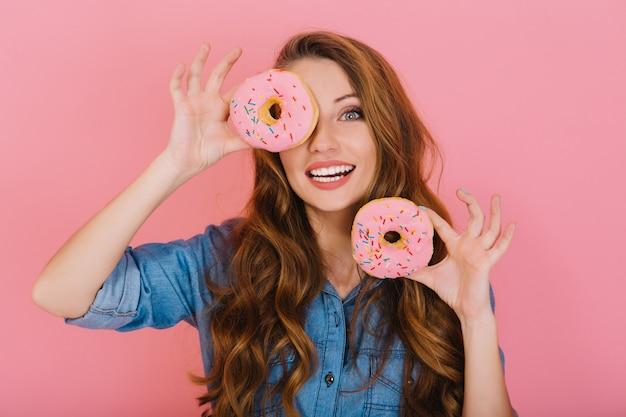 Langhaariges entzückendes mädchen im jeanshemd spielt mit glasierten donuts, bevor es mit freunden tee trinkt. aufgeregte charmante junge frau mit lockigem haar, die glücklich ist, ihre lieblingssüßkrapfen in bäckerei zu kaufen.